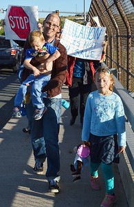 Man at school board protest carries young child, young girl next to him, other marchers with signs behind them.