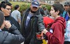 Man wearing Denver Broncos hat reaches for hand warmers being handed out by young boy conversing with woman.