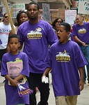 Young African-American man and two young sons, all wearing Justice For Janitors shirts marching, other protesters in background.
