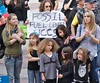 """Two women and 5 young children listen at climate change rally, man behind them with """"fossil fuel divest' sign."""