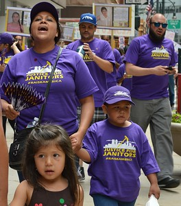 Mother and young son marching in Justice for Janitors march, young girl   in front of them.