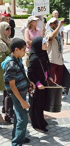 Woman wearing hijab, with drumsticks and drum, young boy standing next to her.