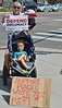 """Mother holding young child and """"Defend Diplomacy""""sign, in front of them, another child in a stroller sitting with legs crossed, in front of stroller sign about supporting Iran treaty."""