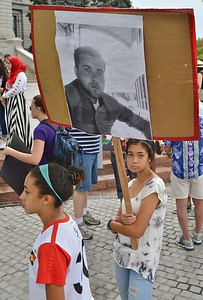 Young girl holding sign with picture of man on it, at palestinian protest.
