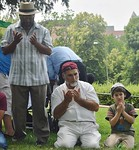 Muslim man with white beard and young boy next to him kneeling in prayer, other man stands and prays next to them.