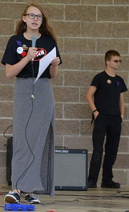 Young girl, a high school student, wearing long skirt, standing on stage, holding a paper and speaking into a microphone, in background, young man dressed all in black.