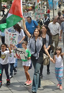 Woman raises Palestinian flag in air, walking with small children, other protesters in background.