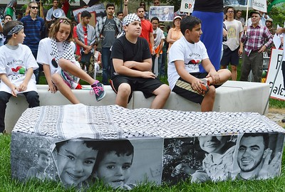 Four young children wearing keffiyehs and Palestine t-shirts, sitting on stone bench, in foreground, mock casket with photographs on it, other protesters in background.