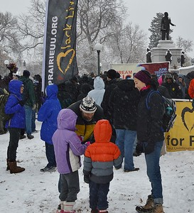 Father speaks to children as they wait in the snow for MLK Day march to begin.