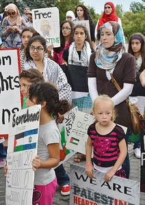 Group of demonstrators at Palestine protest including woman wearing hijab and two young girls holding signs.