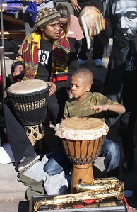 Young African-American boy and man play drums along the MLK Day parade route in Denver.