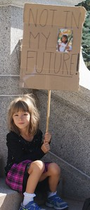 """Young girl sitting on steps holding """"Not In My Future"""" sign at KXL pipeline demonstration."""