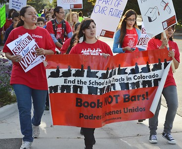 """High school students carry banner """"Books Not Bombs"""", other protester with signs marching in the background."""