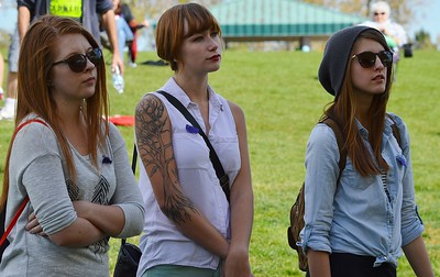 Three young girls, high school students, standing together listening, one with large tatoo of tree on her arm.