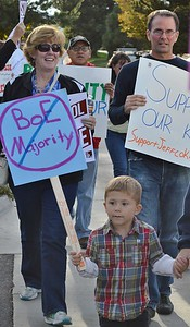 Young boy marching in school board protest with sign, other demonstrators behind him.