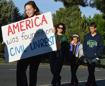"""Young girl smiling while marching at school board protest carries sign """"America Was Founded On Civil Unrest""""."""