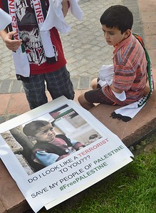 Young boy sitting next to poster about terrorism, with picture of young boy crying on it.