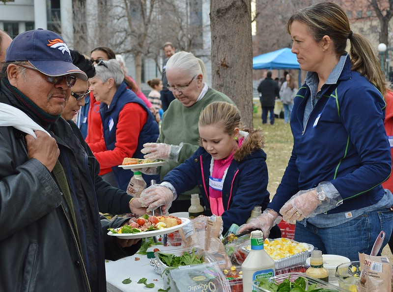 Man wearing Denver Broncos hat holding plate of food at free meal event. On other side of table, woman and young girl serving food to others in line.