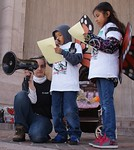 Young hispanic boy speaks at immigration reform rally, woman holding megaphone crouches beside him, young girl next to him.
