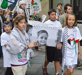 Two young girls carrying mock casket with picture of little boy on it, both wearing keffiyehs, other marchers with signs in background.