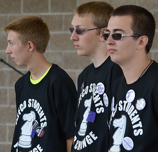 """Three young men, high school students, standing together, all wearing """"Jeffco Students For Change"""" t-shirts."""