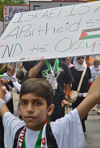 Close-up of young boy with sign about Israel and wearing Palestinian scarf, other marchers in background.