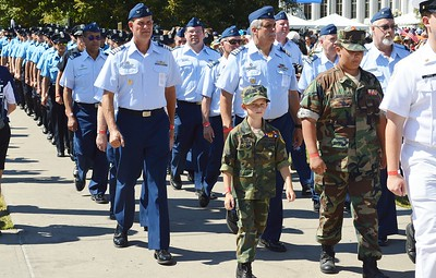 Young boy in Marine uniform marching in 9/11 anniversary commemoration, members of military marching behind him.