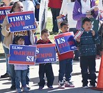 Young children holding signs at immigration rally, one eating a snack.