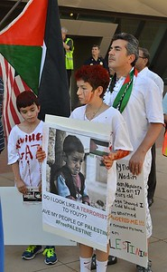 Father and two young sons at protest, boys with fake blood on faces and shirts, Palestinian flag in background.