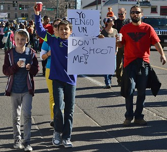 "Two young boys marching in MLK day parade, one holding up sign, ""Don't Shoot Me""."
