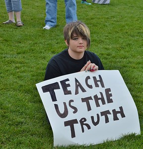 """Young girl, a student, holding sign that says """"Teach Us The Truth""""."""