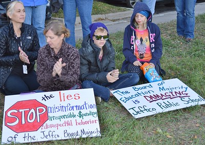 Two women and two children sitting on ground at school board protest signs about lies and misinformation at their feet.