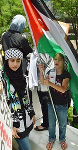Two young girls wearing Keffiyah headbands, one standing under large Palestinian flag she is holding.