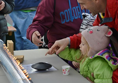 This young girl and her father enjoy one of the hands on exhibits at the March For Science in Denver, Co.