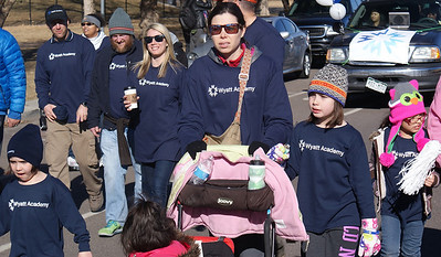 Mother and small children march in the MLK Day parade in Denver.