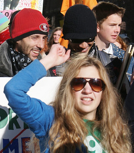 Young woman raises fist at an occupy march in Denver.