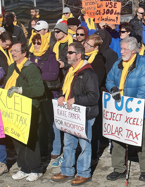 Rooftop solar energy supporters rally in Denver, before marching to the offices of utility corporation Xcel.