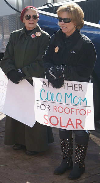 This Colorado mother shows her support for rooftop solar energy,  at a protest at the offices of the utility company, Xcel energy, in Denver.