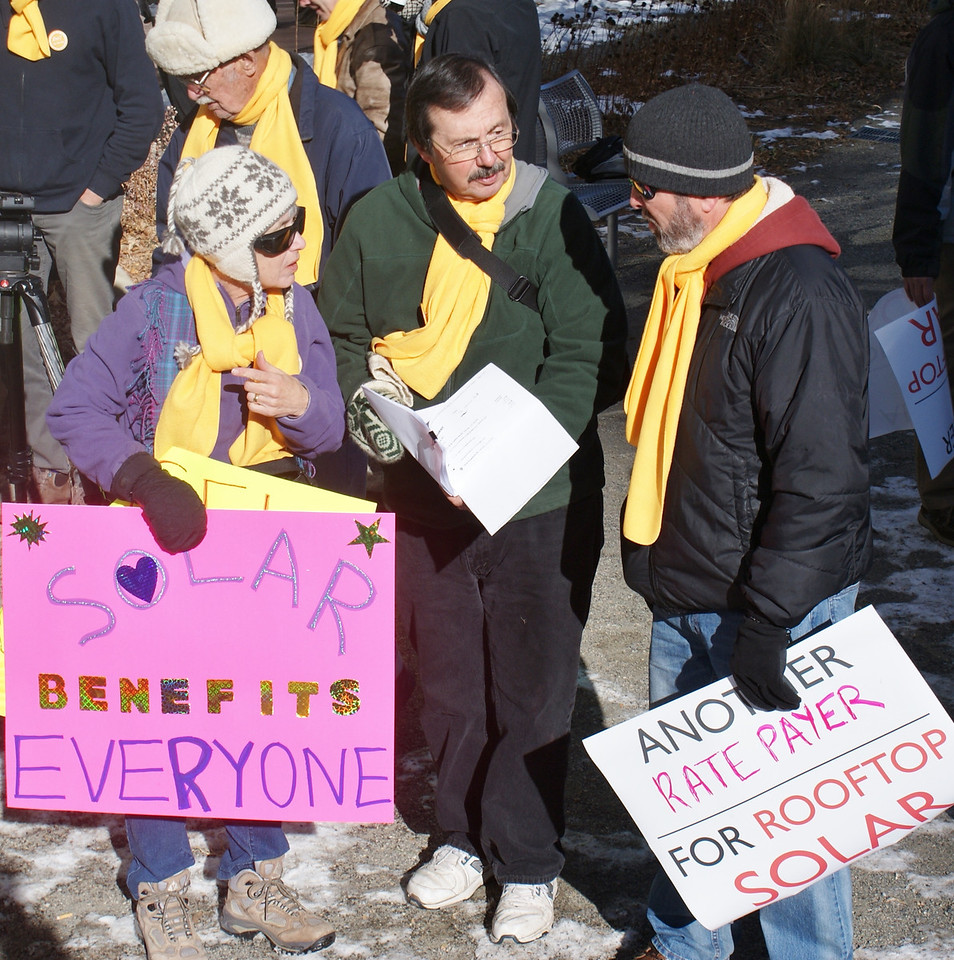 Rooftop solar energy supporters chat before joining a march to the offices of utility corporation Xcel, in Denver.