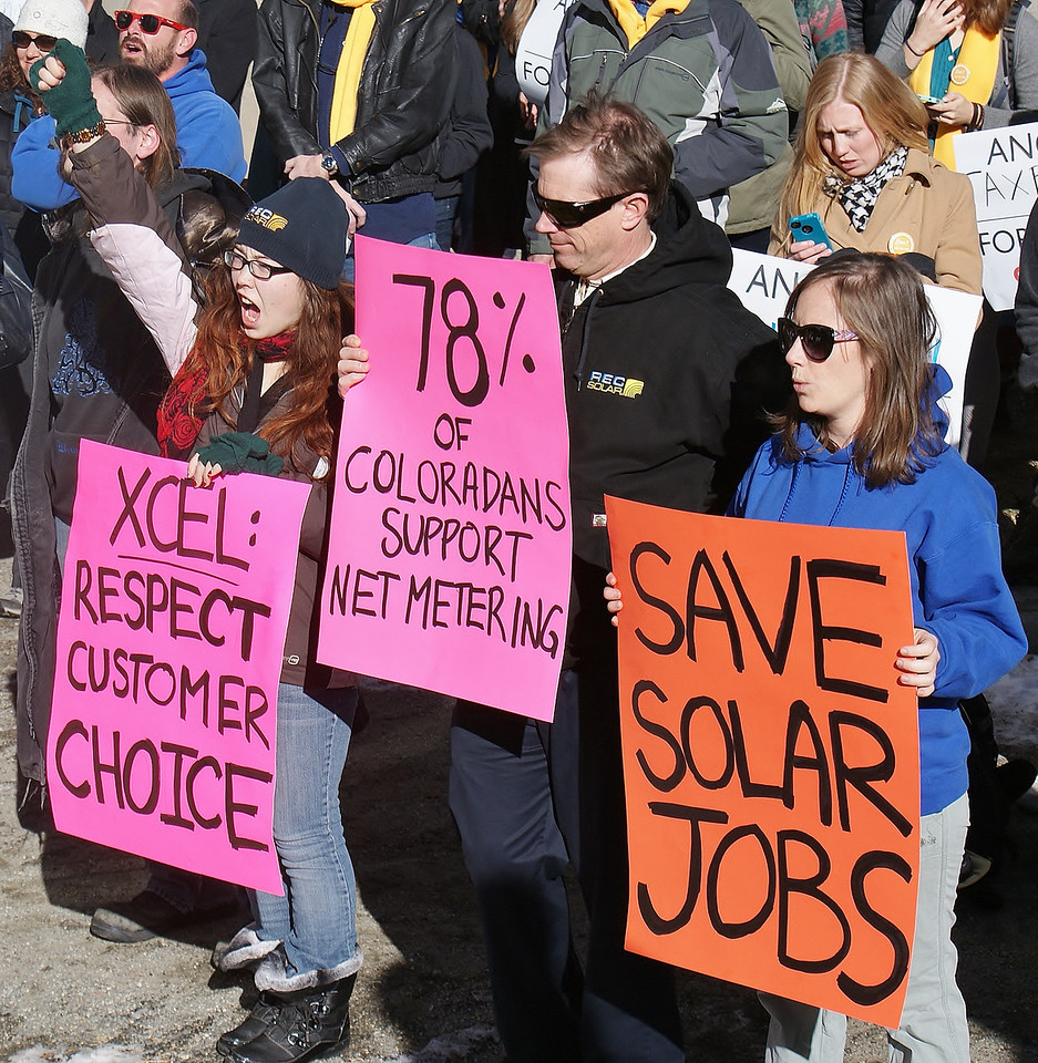 Customers of utility company Xcel Energy demostrate support for rooftop solar near the companies offices in Denver.