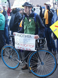 This bicyclist demonstrates support for rooftop solar energy at a protest in Denver at the offices of utility corporation Xcel Energy.