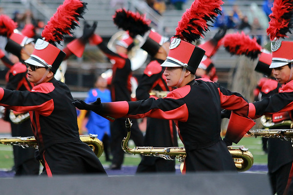 Stacey Diamond | The Goshen News Emmanuel Gomez, Carlos Vivero and Kevin Silva performe hand gestures in formation with their tenor saxophones for the Goshen Crimson Marching Band.