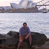 Bayler on the rocks at Mrs. Macquarie's Chair with Sydney Opera House and the Harbour Bridge behind at twilight.