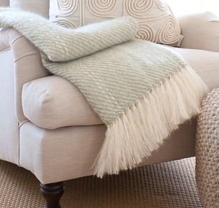 Sage mohari throw classicly folded on linen upholstered chair.