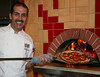 Chef and co-owner Sam Ramaban takes a pizza from the 900 degree brick oven at Boca Pizzeria in Novato, CA on July 9, 2010. It takes four men dedicated just to making pizza to keep up with demand on a warm friday night that he estimated they would make over 400 pizzas.Ramaban's business partner at Boca Pizzeria is Shah Bahreyni.(Special to the IJ/Jocelyn Knight)