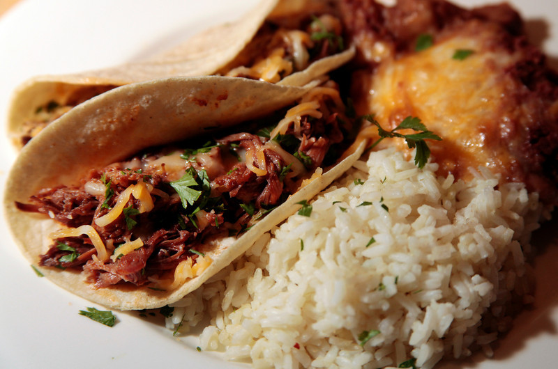 CocaCola Beef Tacos are served with chili lime rice and refried pinto beans with a cheddar/jack cheese mixture. The beef is shredded after being cooked in a sauce that includes CocaCola for twelve hours. Customers pre-order their meal and pick it up in aluminum containers to take home to heat and serve at The White Rose Ranch in Novato, Calif. on Thursday, August 9, 2012.(Special to the IJ/Jocelyn Knight)