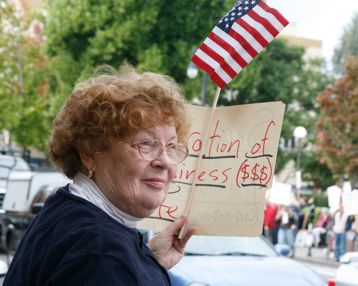 """Joanne Syvertsen of Terra Linda works the other side of the street with her """"Seperation of Buisness $$$ and State"""" sign during the Bank Transfer Day protest in downtown San Rafael, Calif. on Saturday November 5, 2011. (Special to the IJ/ James Cacciatore)"""