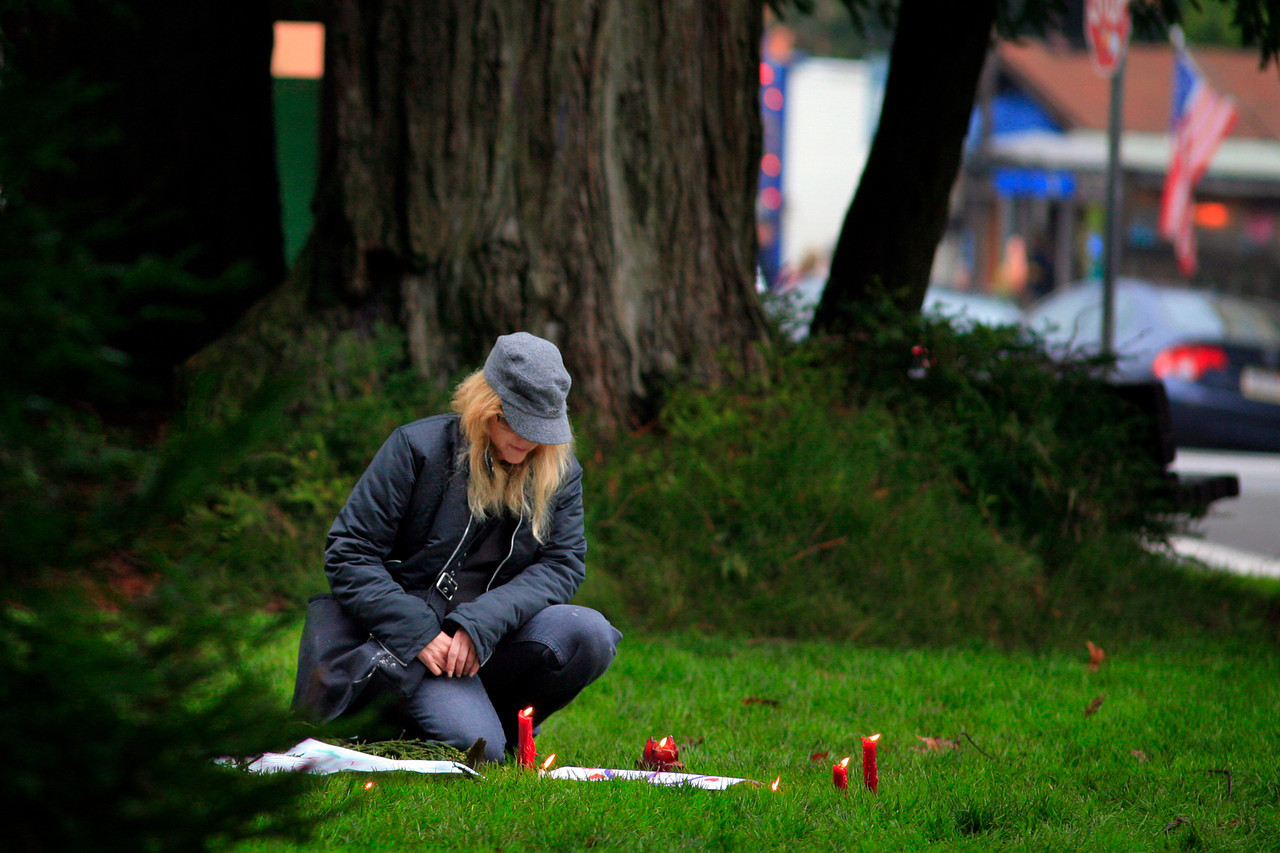 Cyntha from Kentfield takes a moment at the candles brought by people from all over Marin for a vigil to mourn the tragedy in Connecticut at town park in Fairfax, Calif. Saturday, December 15, 2012. (Special to the IJ/James Cacciatore)