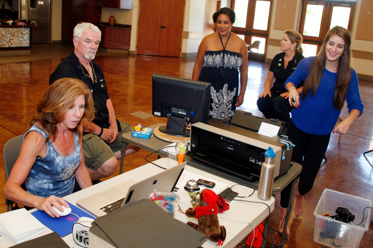 Bambi Buckles, left, sits in for Albert Becker, second from left, to show Denora Montalvan, center, her photographs that Virginia Becker, second from right, just took as Haley Buckles, right, assists for The Family Album Project at Homeward Bound in Novato, Calif. on Sunday,  June 10, 2012. (Special to the IJ/ James Cacciatore)
