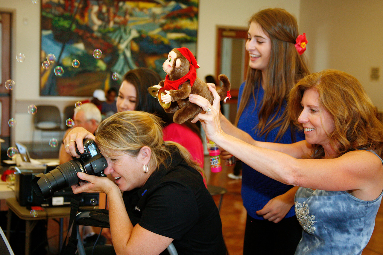 Bambi Buckles, right, and her daughter Haley, second from right, pull out all the stops to get a smile from one of the children being photographed by Virginia Becker of The Family Album Project at Homeward Bound in Novato, Calif. on Sunday,  June 10, 2012. (Special to the IJ/ James Cacciatore)